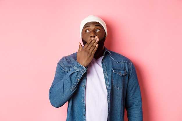 Uomo afroamericano scioccato ansimando, fissando a sinistra in soggezione, spettegolando, in piedi su sfondo rosa