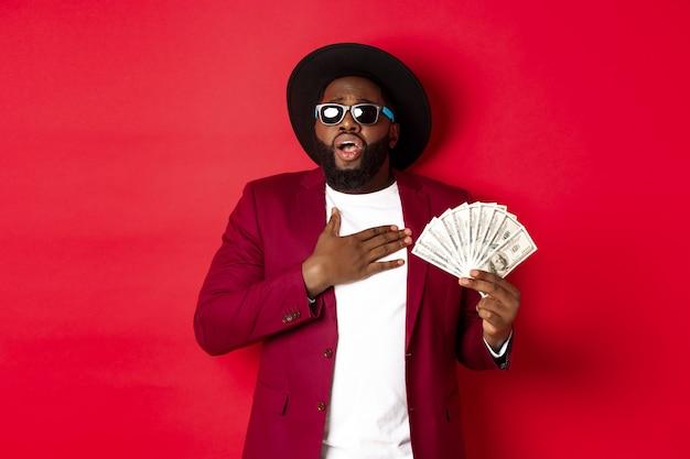 Uomo afroamericano scioccato che tiene la mano sul cuore e ansima per l'eccitazione, mostrando un'enorme quantità di denaro, vincendo il premio, in piedi su sfondo rosso.