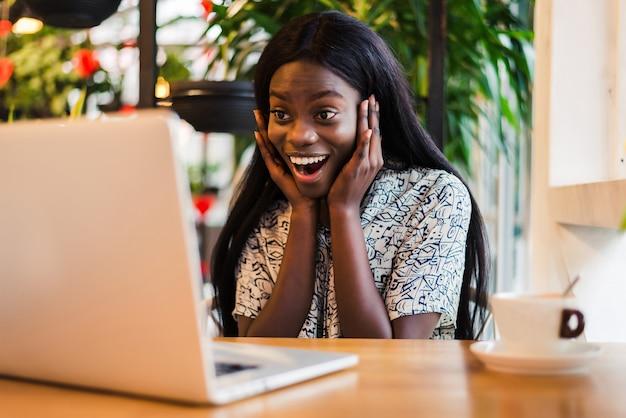 ショックを受けたアフリカの女性フリーランサーは、バグのある目でラップトップコンピューターを見つめます