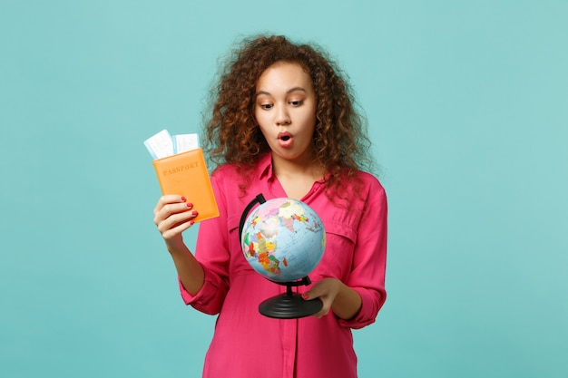 Shocked african girl in casual clothes holding earth world globe, passport boarding pass ticket, isolated on blue turquoise background. people sincere emotions, lifestyle concept. mock up copy space.