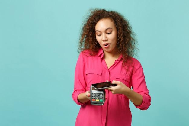 ショックを受けたアフリカの女の子は、青いターコイズブルーの背景に分離されたクレジットカード決済の取得を処理するために携帯電話のワイヤレス現代銀行決済端末を保持しています。人々のライフスタイルの概念。コピースペースをモックアップします。