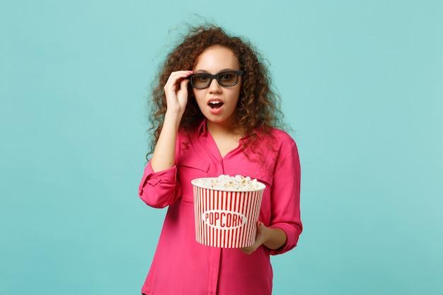 3d 아이맥스 안경을 쓴 아프리카 소녀가 영화를 보고 스튜디오의 파란색 청록색 벽 배경에 격리된 팝콘을 들고 충격을 받았습니다. 영화, 라이프 스타일 개념에서 사람들의 감정. 복사 공간을 비웃습니다.