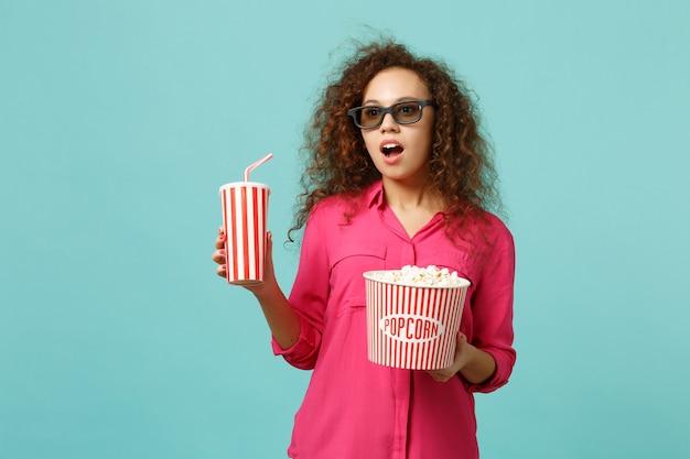 3d 아이맥스 안경을 쓰고 영화를 보고 있는 아프리카 소녀는 스튜디오에서 파란색 청록색 배경에 격리된 팝콘, 탄산음료 한 잔을 들고 있습니다. 영화, 라이프 스타일 개념에서 사람들의 감정. 복사 공간을 비웃습니다.