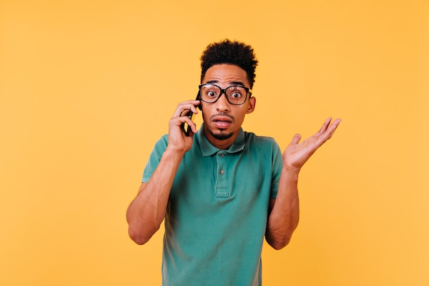 전화 통화하는 큰 안경에 충격 된 아프리카 남자. 스마트 폰으로 포즈를 취하는 감정적 인 곱슬 남자의 초상화.