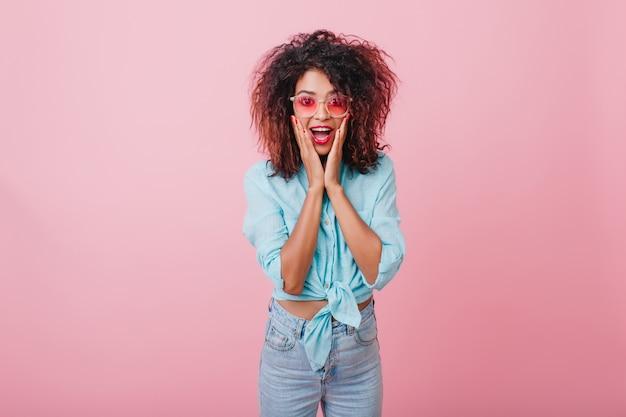 놀란 감정을 표현하는 곱슬 헤어 스타일로 충격을받은 아프리카 아가씨. 그녀의 얼굴을 만지고 데님 바지에 놀라운 스포티 한 흑인 여성의 실내 초상화.