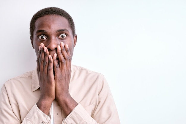 Shocked african man stand in fear, frightened by something, closing mouth and looking at camera, isolated on white wall