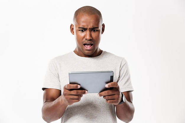 Shocked african man using tablet computer