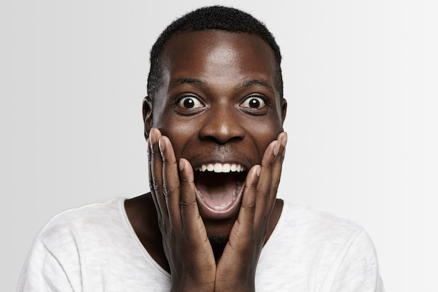 Shocked african student or employee   in full disbelief, hands on cheeks, mouth wide open, surprised with some unexpected news or big sale prices.