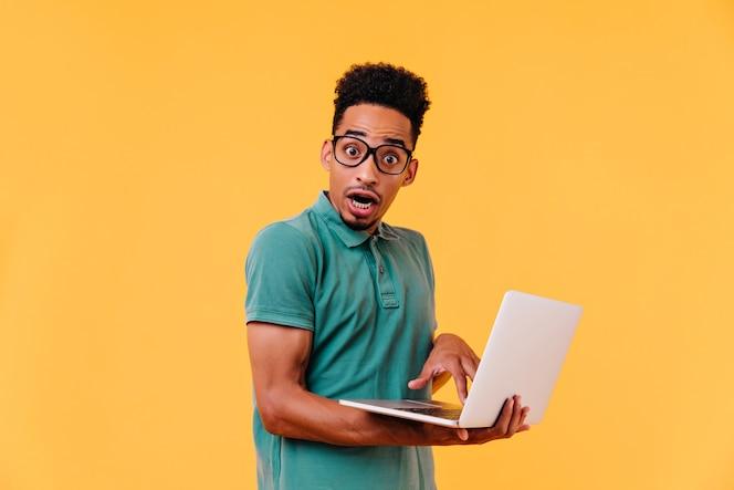 宿題をしながらポーズをとるショックを受けたアフリカの学生。がっかりしたブルネットのウェブ開発者。