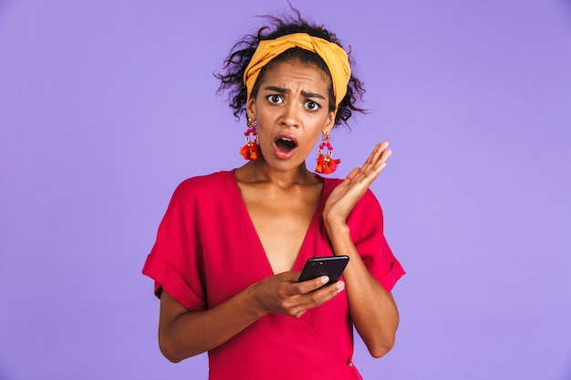 Shocked african woman in dress holding smartphone over purple wall