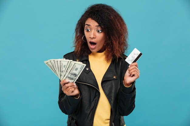 Shocked african woman in leather jacket holding credit card