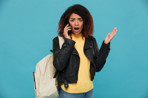 Shocked african woman in leather jacket with backpack