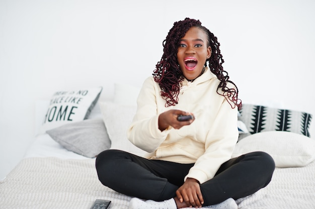 家でテレビを見て、ベッドでリモコンを持って口を開けてショックを受けたアフリカの女性