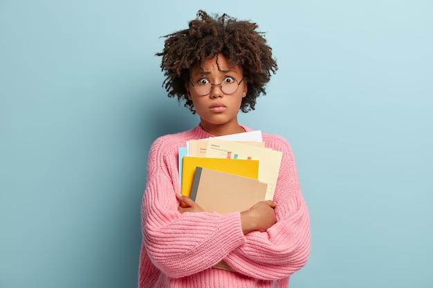Studente universitario afroamericano scioccato sta in piedi con i libri di testo, afraids di superare l'esame
