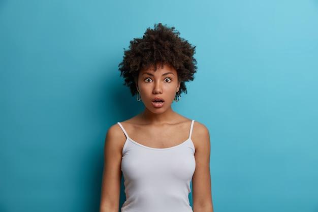 충격을받은 아프리카 계 미국인 여성이 캐주얼 한 옷을 입고 놀랍게도 턱을 떨어 뜨리고 말을하지 않고 불신의 표정으로 큰 눈을 쳐다 보며