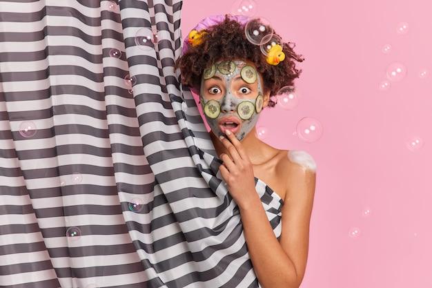 Шокированная афроамериканка выглядит с большим удивлением, смотрит широко открытыми глазами, применяет косметическую маску для ухода за кожей, принимает душ, изолированные над розовыми мыльными пузырями на стене.