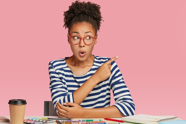 Shocked afro american woman thinks on blueprint creation, makes illustration with crayons