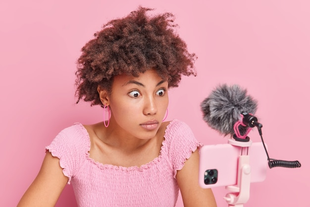 Shocked afro american woman with curly hair stares at phone webcam records live stream video has online training courses