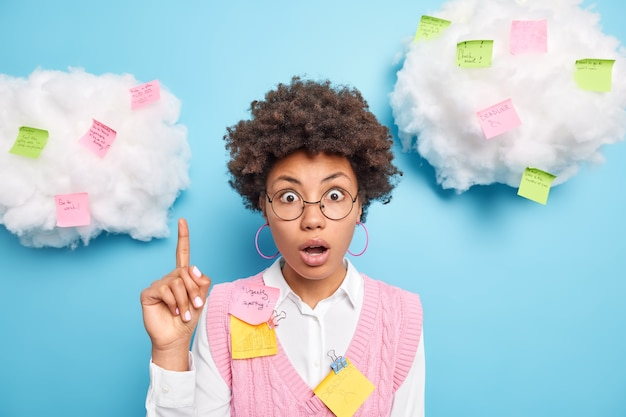 Shocked afro american woman works in office works on marketing project points above with stunned expression on white clouds surrounded by colorful sticky notes