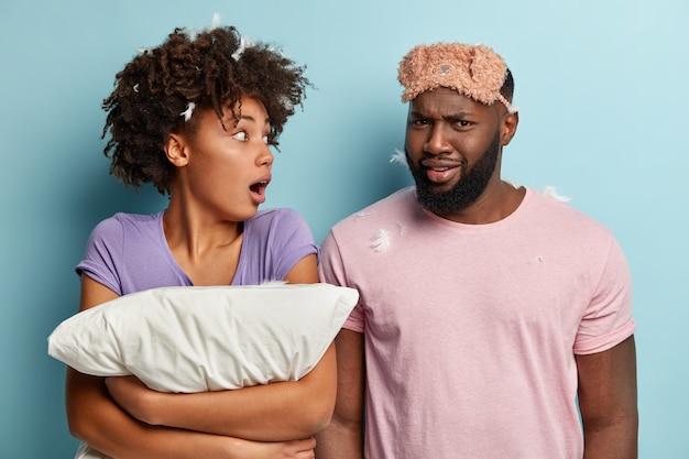 충격을받은 아프리카 계 미국인 젊은 여성이 남편을 크게 놀라게 쳐다보고 부드러운 베개를 단단히 들고 분개하고 어두운 피부를 가진 남자가 이마에 아이 마스크를 쓰고 불쾌감을 느낍니다.