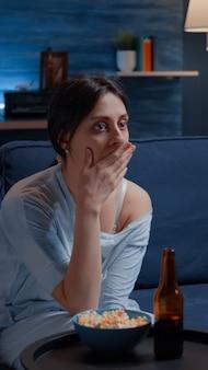 Шокированная, изумленная, изумленная женщина смотрит фильм по телевизору с удивленным выражением лица, ест поп ...