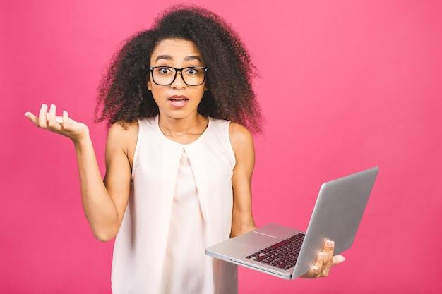 ショックを受けて驚かれるビジネスや学生の女性、ピンクのポーズ。コピースペースのモックアップ。ラップトップpcコンピューターでの作業。