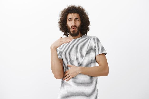 Шокированный изумленный восточный парень с бородой, машет ладонью и хмурится