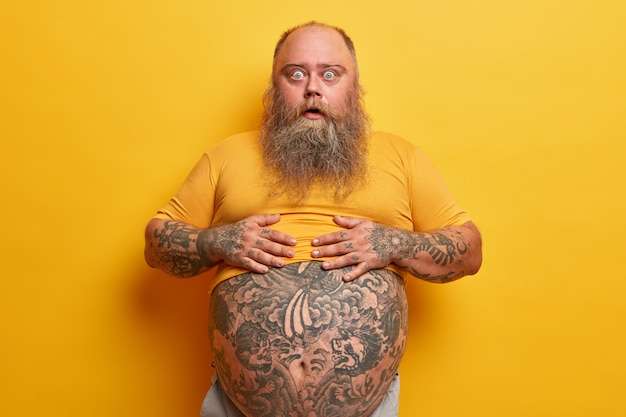 Shocked amazed hipster man keeps hands on belly with tattoo sticking out from t shirt, surprised to find out his weight, has long thick beard, poses against yellow wall. guy shows big abdomen
