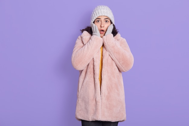 Shocked amazed surprised excited young woman wearing warm fur coat and cap, standing against lilac wall and covering cheeks with hands, looking at camera with big eyes.