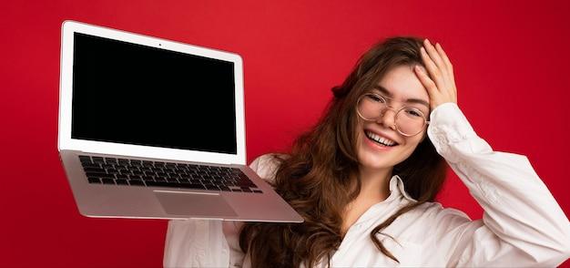 컴퓨터 노트북을 들고 와우라고 말하는 아름다운 갈색 머리의 곱슬곱슬한 젊은 여성이 놀라움을 금치 못했습니다