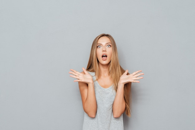 Shocked amazed young woman with raised hands and opened mouth over gray background