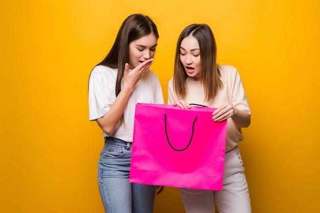 黄色の壁に隔離されたポーズのデニムの服の眼鏡でショックを受けた驚いた若い女性の女の子の友人。人々の誠実な感情のライフスタイルの概念。買い物後に購入したパッケージバッグを保持する