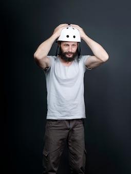 自転車の保護ヘルメットをかぶって立って頭に手をかざしてショックを受けたアメリカ人のハンサムなひげを生やした男。頭に白いヘルメットをかぶったロシアのバイカーがそれを滑らせます。びっくりした表情、表現