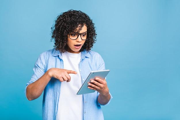 텍스트, 로고 또는 광고 복사 공간이 격리 된 파란색 배경 위에 디지털 태블릿을 들고 곱슬 아프리카 머리를 가진 충격 된 미국 학생 소녀.