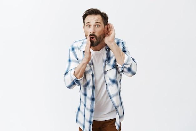 Шокированный и пораженный бородатый зрелый мужчина позирует