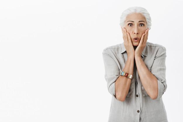 Шокированная и изумленная бабушка выглядит изумленной, белый фон