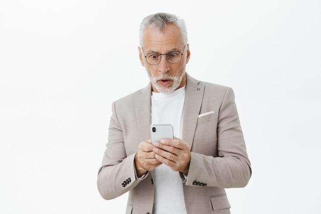 Шокированный и удивленный старик смотрит на экран мобильного телефона