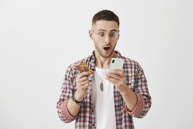 彼の電話とカードでポーズをとっている眼鏡をかけたショックを受けて驚いた若い男