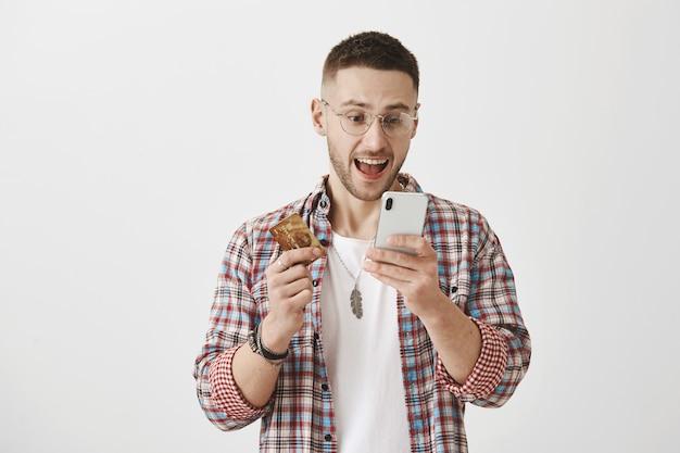 Шокированный и изумленный молодой парень в очках позирует со своим телефоном и картой