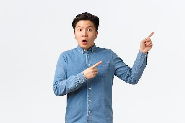 製品や発表について質問するショックを受けて驚いたアジア人男性。驚いたように見える男、好奇心旺盛な右上隅の指を指して、大きなイベント、白い背景について話し合っています。