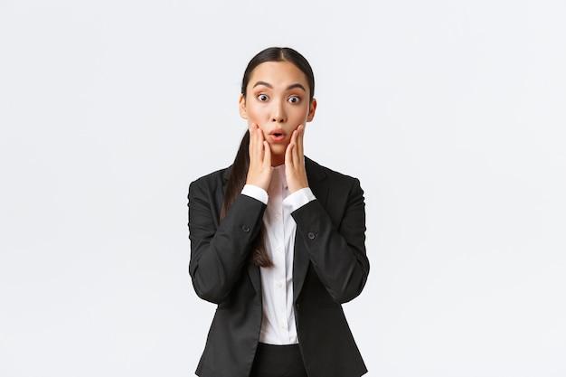 Шокированная и изумленная азиатская бизнес-леди слышит важные новости. продавщица получает шокирующие новости, стоя в костюме, изумленно глядя в камеру, подписывая крупную сделку с деловыми партнерами.