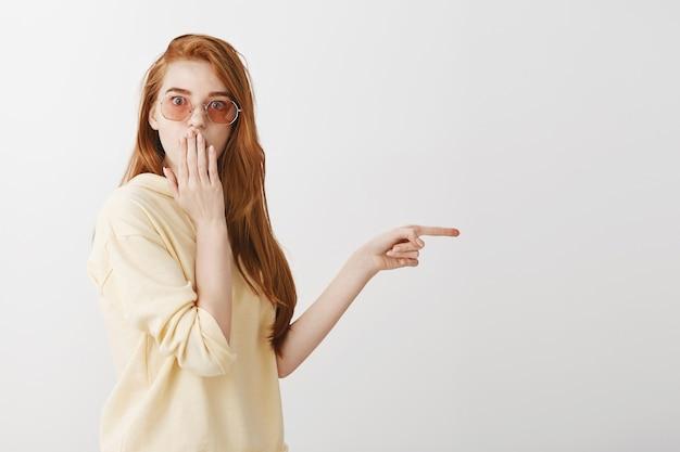 충격과 놀란 빨강 머리 소녀 오른쪽 손가락을 가리키고 헐떡이며 놀랐습니다.