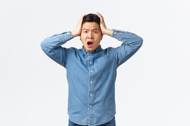 ショックを受けて心配しているアジア人男性が頭をつかみ、パニックと否定でそれを振る。ひどい状況に直面し、不安と不安に立ち、何をすべきかわからず、優柔不断に感じ、助けが必要な男。