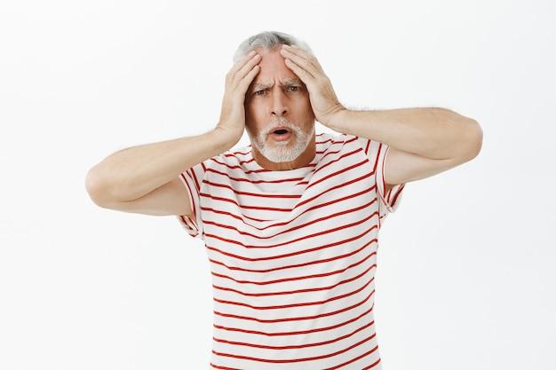 Шокированный и обеспокоенный старший мужчина в панике, выглядя обеспокоенным