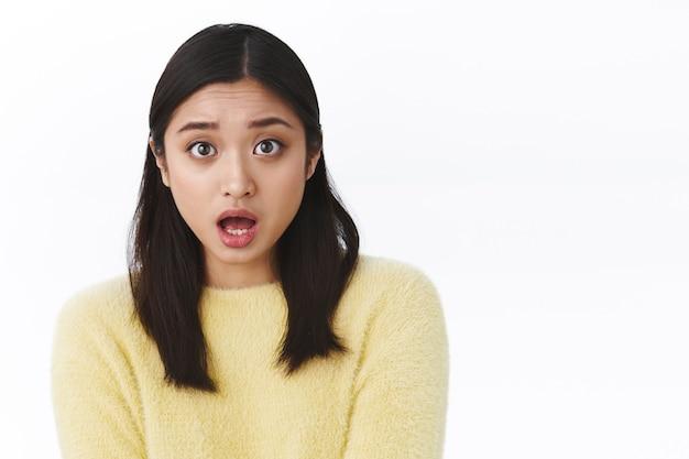 Потрясенная и обеспокоенная молодая азиатская девушка с открытым ртом, встревоженная задает вопрос, жалко, что друг попал в беду, смотрит с состраданием, узнает ужасные новости, белая стена