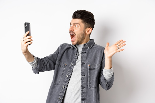 Шокированный и сбитый с толку человек разочарованно смотрит на экран смартфона, кричит от разочарования, стоя на белом фоне.