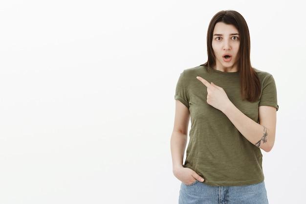 Шокированная и сбитая с толку нервная девушка, задыхаясь от разочарования и указывая в левый верхний угол, спрашивает, спрашивает, что случилось, с встревоженным и встревоженным выражением лица, обеспокоенная серой стеной