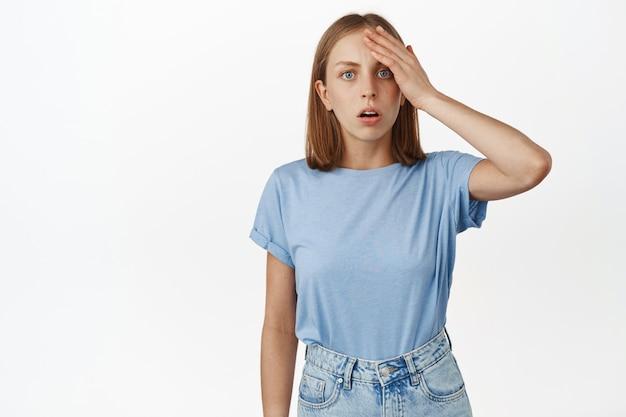 충격을 받고 혼란스러운 여성이 머리에 손을 대고 어리둥절한 표정으로 정면을 응시하고 중요한 것을 잊어버리고 무슨 일이 일어났는지 이해하지 못하고 흰 벽에 기대어 서 있습니다