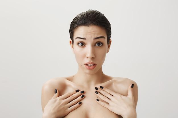 裸で立って、何かで非難されている自分を指してショックを受けて混乱している女性