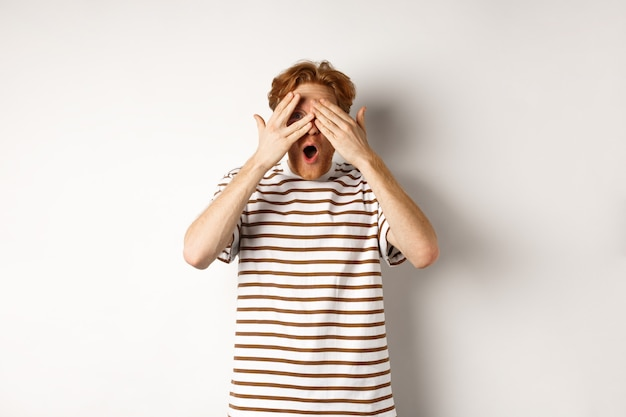 ショックを受けて恥ずかしい赤毛の男が目を覆い、指をのぞき、あえぎ、白い背景の上に立っています。